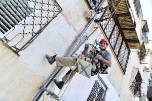 תיקון צנרת בבניין בגובה תוך כדי תלייה עם ציוד סנפלינג - תמונה מלמטה