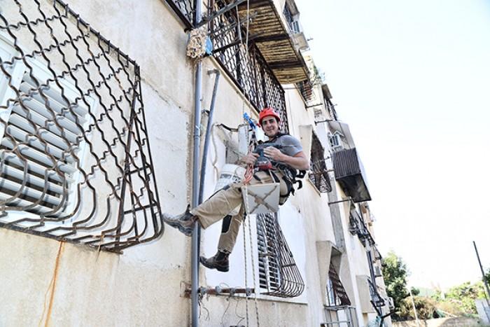 תיקון צנרת בבניין בגובה תוך כדי תלייה עם ציוד סנפלינג -