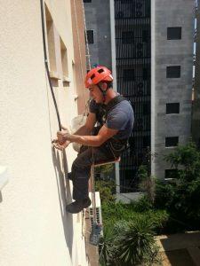 אלירן האינסטלטור: תיקון אינסטלציה בסנפלינג בתלייה מגג בניין - תמונה מהצד א.א. ארהם